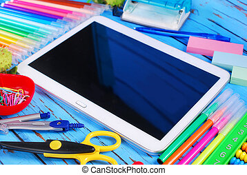 school time - tablet pc and various school equipment on blue...