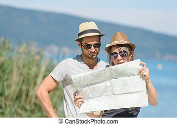 a young couple, looking at a map