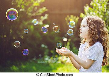 little girl catches soap bubbles