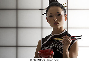 oriental girl with chopstick - nice back light shot of a...