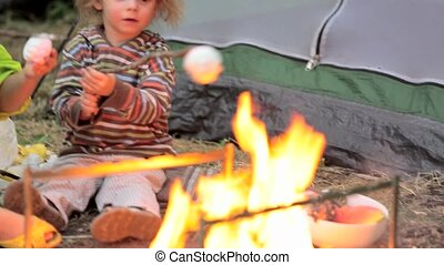 The boy and the girl fry a zephyr on a fire. - Tent town in...