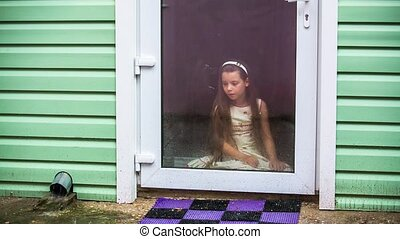 Sad Girl Sitting At Glass Door And Looking At Rain - Little...