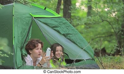 Girls and the little boy admire the nature lying in tent.