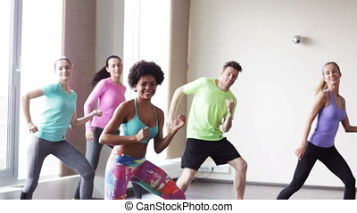 group of smiling people dancing in gym or studio - fitness,...