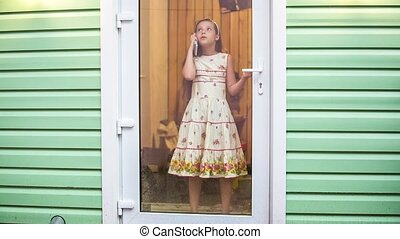 Cute Girl Standing At Door And Talking On Cellphone - Cute...