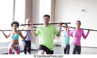 group of people exercising with bars in gym - fitness,...