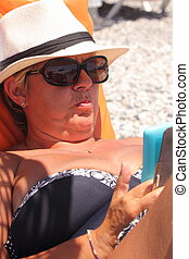 On vacation - A mature woman wearing a hat and sunglasses...