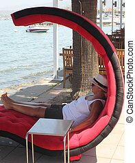 On vacation - A blond mature woman relaxing on a large chair...