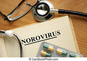 Word Norovirus on a paper and pills on the wooden table.
