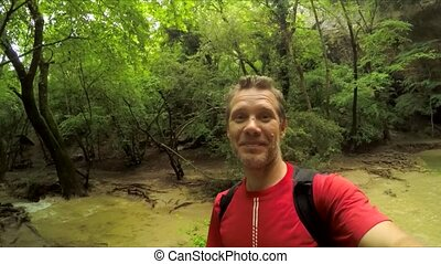 Man Making Selfie Video At Waterfall - This is a portrait of...