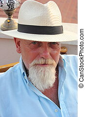 An englishman with a beard wearing a hat while on vacation