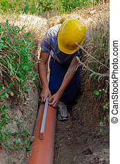 Sewerage - Worker at connecting sewer pipes to measure the...