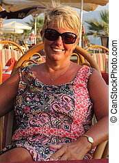 On vacation - A blond mature woman wearing sunglasses while...