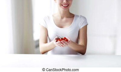 close up of young woman showing cherry tomatoes - healthy...