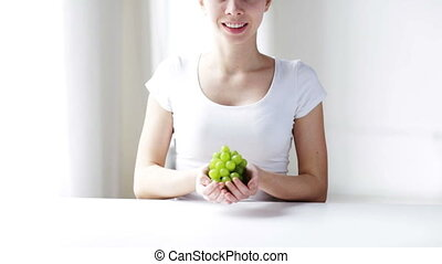 close up of young woman showing green grape bunch - healthy...