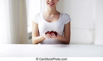 close up of young woman showing strawberries - healthy...