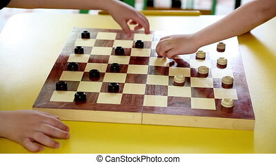 Children Playing Checkers at The Table Age 5 Years