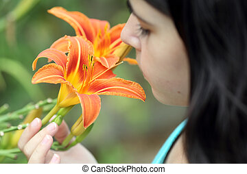 Lilium and girl - Detail of a girl smelling a beautiful...