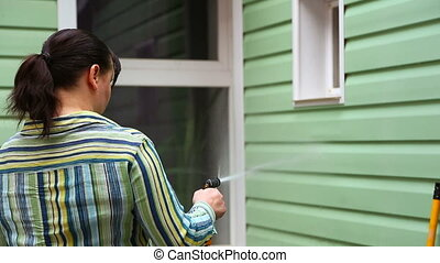 Woman Washing Wall Of House With Sprayer - In the frame...