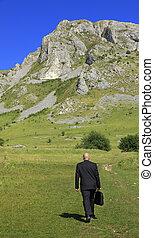 Businessman outdoors - Businessman oudoors walking through a...