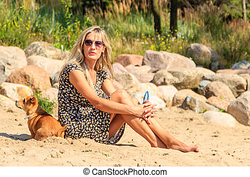 Happy woman sun tanning and relaxing on beach.