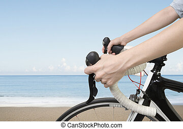 Closeup on woman hands riding a bike, with blue sky sea...