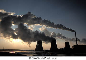 View of coal powerplant against sun and huge fumes