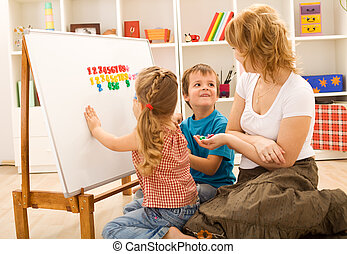 Kids doing math exercises with mom - Preschool kids sitting...
