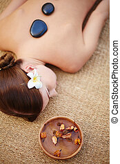 During lastone therapy - Lying woman during lastone massage