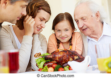 Family dinner - Portrait of family of four with roasted...