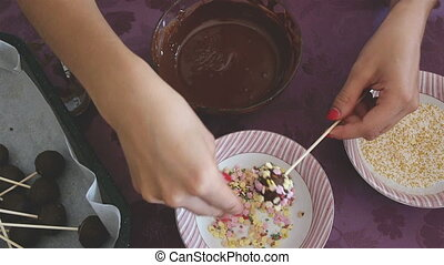 Woman making chocolate cakepops wit - Woman making colorful...