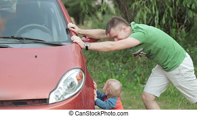 Dad and son are repairing car - Nature dad with his son,...