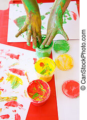 Child dipping fingers in non-toxic finger paints - Child...