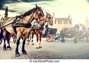 Horse-drawn carriages on the Old Market square. Bruges,...