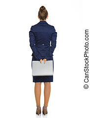 Businesswoman seen from behind holding file behind her -...