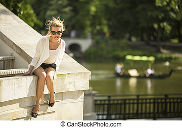 woman sitting near the water - An attractive young blond...