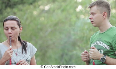 Couple smoking hookah in nature - In Nature couple of smokes...