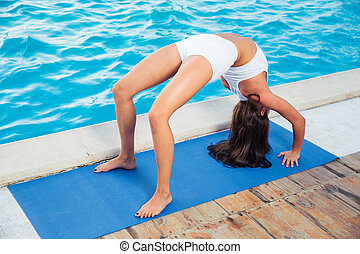 Woman doing yoga bridge pose outdoors - Portrait of a young...