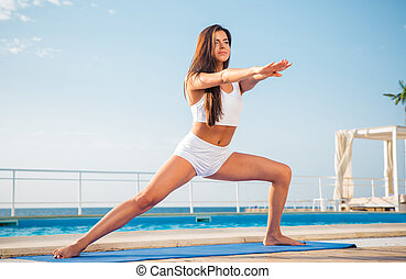 Woman doing stretching exercises on yoga mat