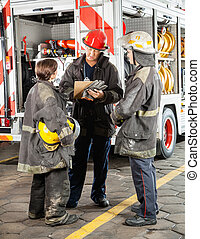 Firefighters Discussing Over Clipboard At Fire Station -...