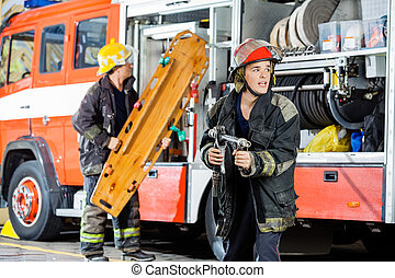 Alert Firefighter Holding Hose While Colleague Carrying...