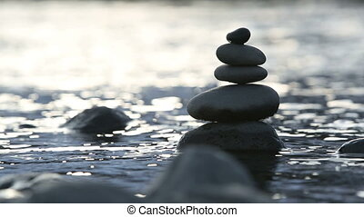 Stones in water stacked as a tower
