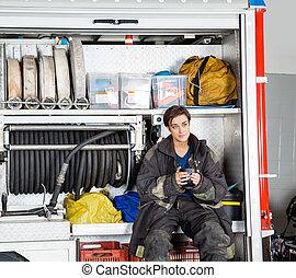 Thoughtful Firewoman Holding Coffee Mug In Truck -...