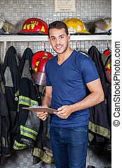 Smiling Firefighter Holding Clipboard At Fire Station -...