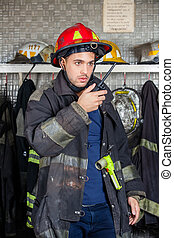 Firefighter Using Walkie Talkie At Fire Station - Young male...