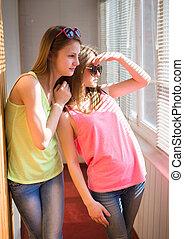Two pretty teenage girls having fun in sunroom - Closeup...