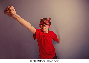 Boy teenager twelve years in red shirt in mask, super hero...