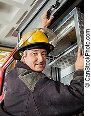 Confident Fireman Climbing Truck
