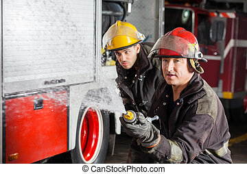 Firemen Spraying Water During Training - Confident young and...