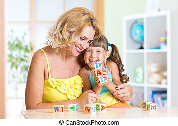 Mother and her daughter playing with cubes at home